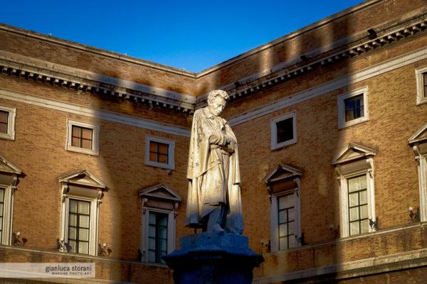 La statua di Leopardi illuminata dal sole e l'ombra della torre di Recanati