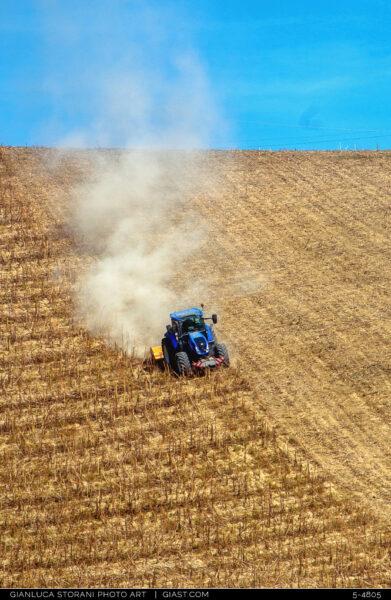 Un trattore tra polvere e fumo nella campagna maceratese